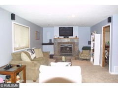 Lower level family room with a gas fireplace. The laundry room is the doorway off to the right.
